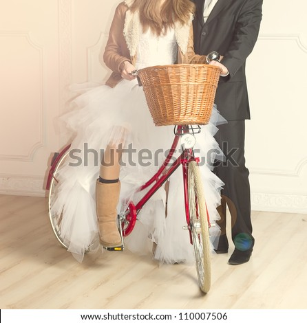 groom and bride in wedding suit standing beside old bicycle