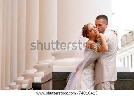 Groom and bride kiss near Wedding palace - stock photo
