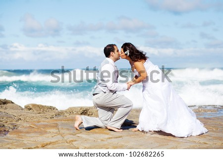 groom and bride kissing on beach rocks