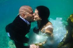 groom and bride kissing underwater