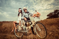 Groom and bride on a bicycle with just married sign and cans attached