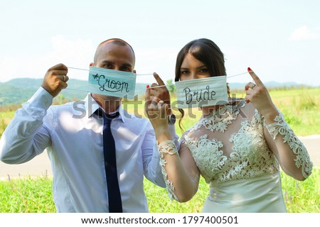 Groom and Bride wear/show medical face masks with the inscription 'groom' and 'bride' on their wedding day in nature during the COVID-19 virus. Photo shooting wedding day during the Coronavirus. Foto stock ©