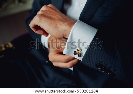 Groom buttoning a shirt on  white wedding