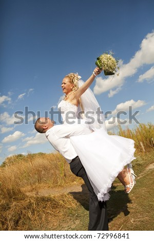 Groom carrying bride in his arms in eared field