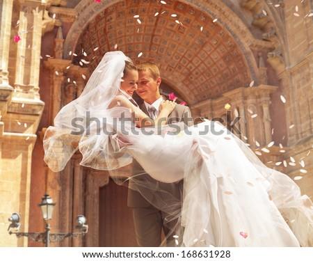 groom carrying bride near church