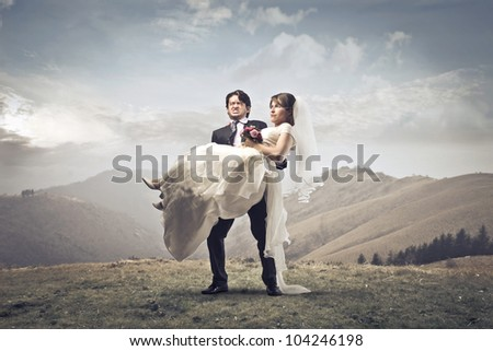 Groom carrying his wife in his arms on a hill