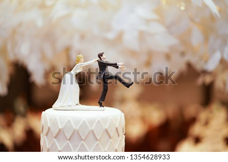 groom doll and statue is running away but bride can catch him finally. the funny wedding story doll on the top of cake.