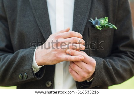 Groom fit on his wedding ring on right hand. Close-up of man in suit hands fidgeting golden wedding ring