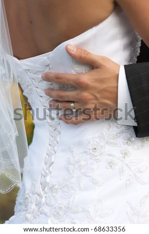 Groom hand on brides dress at wedding dance - stock photo