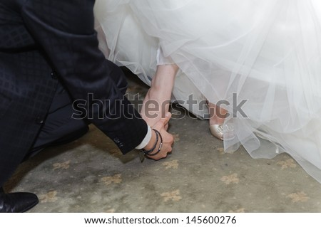groom helping bride to put on shoe - stock photo