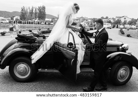 groom helps the beautiful bride to leave the car