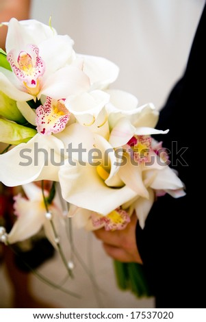 groom holding a bouquet of orchids and lilies