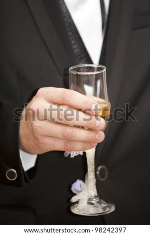 Groom holding a glass with champagne with decorative flowers