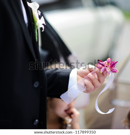 Groom holding boutonniere