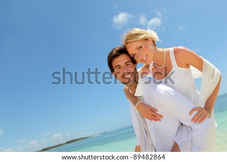 Groom holding bride on his back