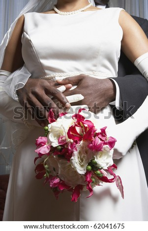 Groom holding his bride's waist - stock photo