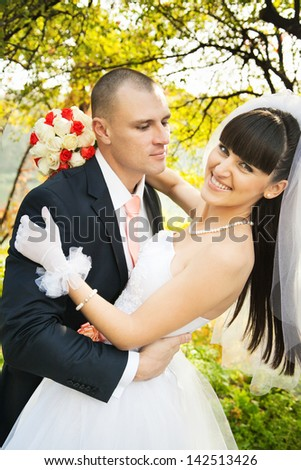 Groom holding leaning smiling bride against yellow leaves background