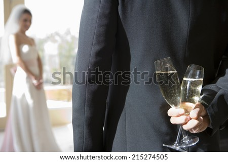 Groom holding two champagne flutes behind back, bride standing in background, focus on groom in foreground, rear view