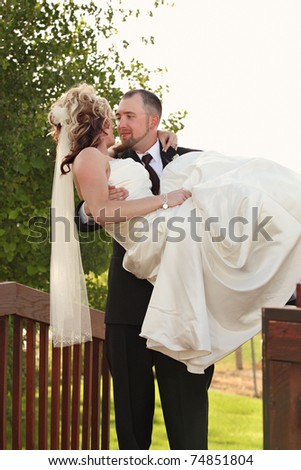 groom holding young bride with faces close outdoors