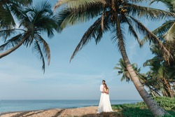 Groom hugs bride's shoulders while kissing her on the shore under palm trees. Happy newlyweds stand holding hands on the background of the blue sea. Wedding walk on a sand beach