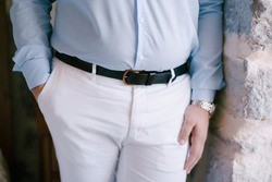 Groom in a shirt and trousers stands near a stone wall