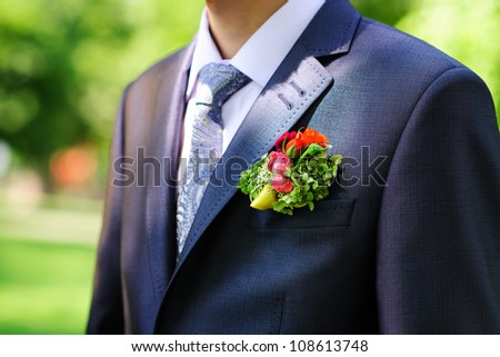Groom in black suit wearing buttonhole