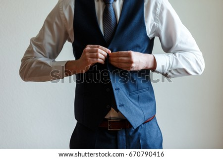 Groom in blue suit and tie getting ready in the morning. The young man fastens the buttons of the jacket, close-up #670790416