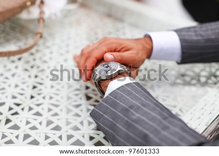 Groom in serious luxury costume is checking the time. He\'s sitting at the table and waiting for a bride.