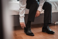groom in white shirt and black pants sitting on the bed putting on black shoes for the wedding