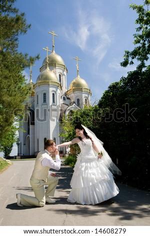 groom kisses hand of bride near the church