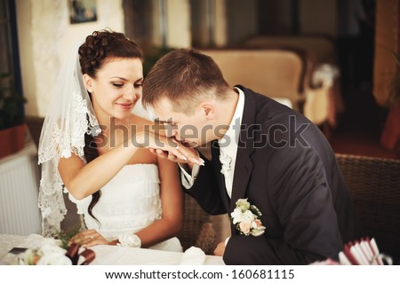 Groom kissing hand of his lovely bride.