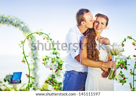 groom kissing his bride on wedding day near floral arch on wedding venue