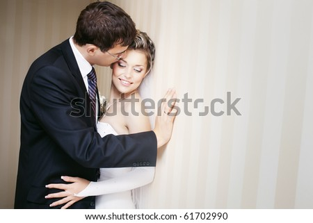 groom kissing smiling bride in the cheek indoors with copy space