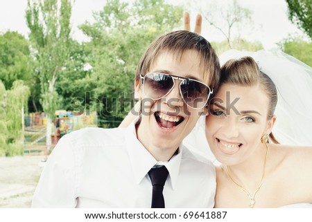 Groom laughing in sunglasses and bride showing tongue and doing rabbit ears