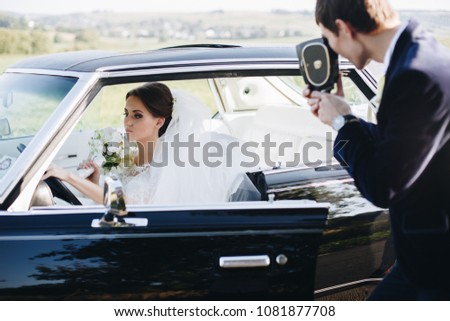 Groom making photo of beautiful bride in wedding dress with flover bouquet on the old vintage, retro camera. Bride woman sitting in luxury retro car. Wedding photoshoot