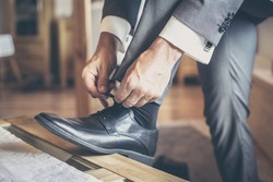 Groom on wedding binds up the shoes, detail