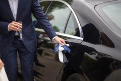 Groom opening the luxury wedding car doors for the bride
