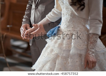 Groom puts a wedding ring on delicate bride's hand covered with laces #458757352