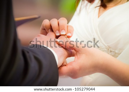 Groom puts ring on brides finger in church