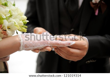 groom puts wedding ring on bride's finger