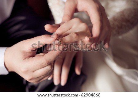 Groom putting a ring on bride's finger during wedding ceremony