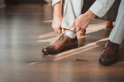 groom putting his wedding shoes. Hands of wedding groom getting ready in suit