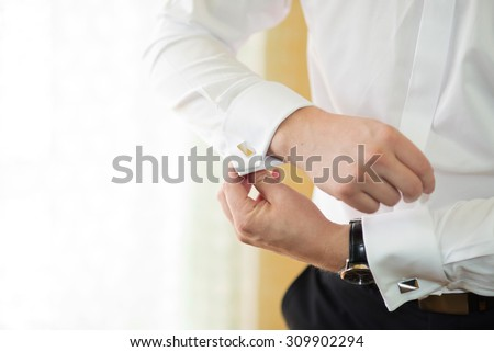 groom putting on cuff-links as he gets dressed in formal wear close up, close up of a hand man how wears white shirt and cufflink