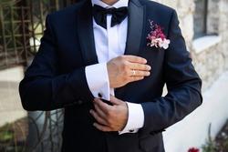 groom's wedding preparation straightens cufflinks
