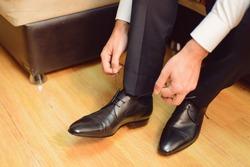groom straining laces on wedding shoes