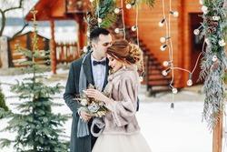 Groom tenderly embracing her beautiful bride. Winter wedding ceremony in rustic style outdoors.
