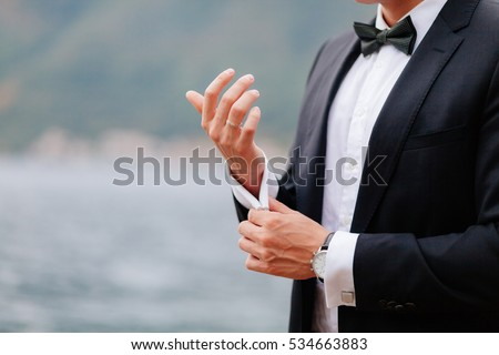 Photo of groom wear cufflink close up shot with sea view