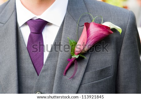 groom wearing a purple lily buttonhole - stock photo