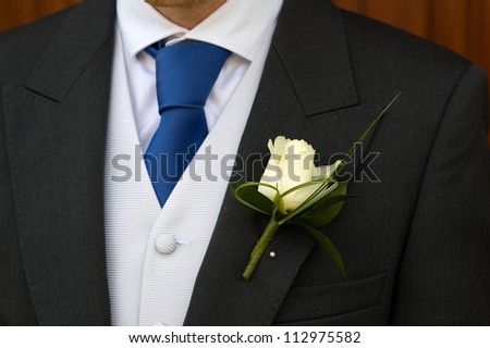 groom wearing a white rose buttonhole at a wedding