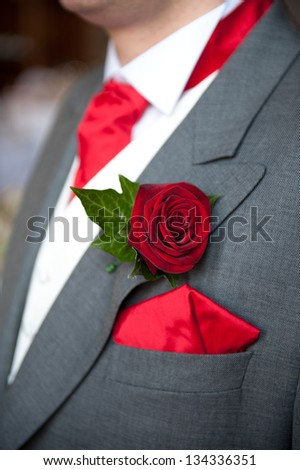 groom wearing red rose buttonhole at wedding